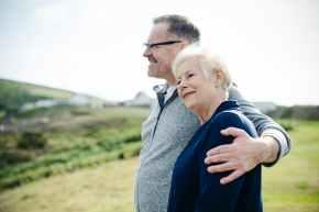 smiling man holding woman s left shoulder