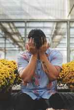 man in floral shirt covering his face with his hands sitting between potted yellow flowers